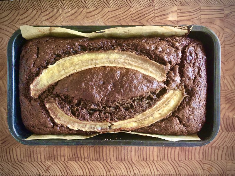 A loaf of buckwheat banana bread sits in its pan on top of a wooden cutting board.