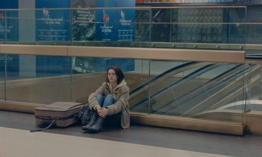 a young woman sits on the floor of penn station