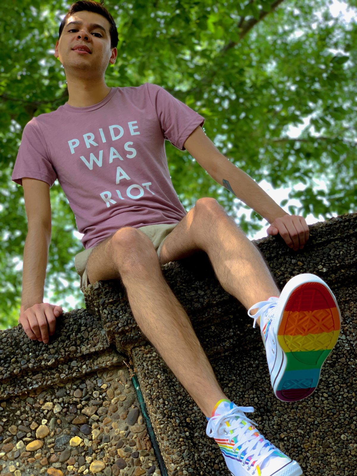 "Jose Munoz poses in a T-shirt that says, ""Pride was a riot."" The soles of his sneakers are rainbow-colored."
