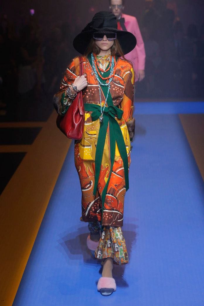 A model walks the Gucci runway in a colorful outfit.