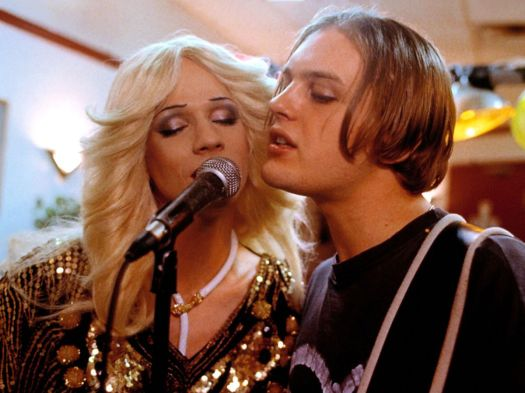 John Cameron Mitchell and Michael Pitt sing into a mic together in Hedwig and the Angry Inch