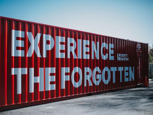 """A red shipping crate is adorned with white letters reading """"Experience the Forgotten."""""""