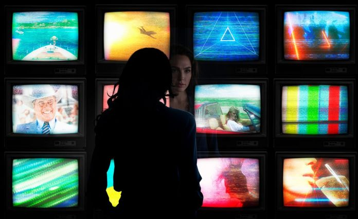 Diana Prince (Gal Gadot) looking at a wall of 12 TVs in Wonder Woman 1984