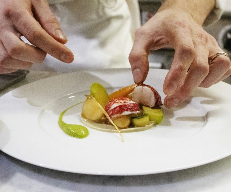 A chef places thick cuts of lobster in a bed of other ingredients on a mostly clean white plate