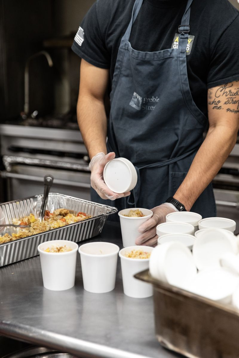 A man with tattooed arms fills to-go containers with rice and eggs