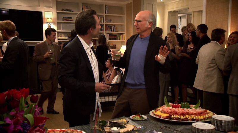 Larry David and Christian Slater argue over caviar in a scene from Curb Your Enthusiasm.