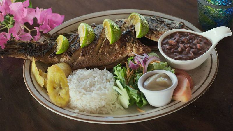 A large fried fish sits on a plate with other Costa Rican sides.
