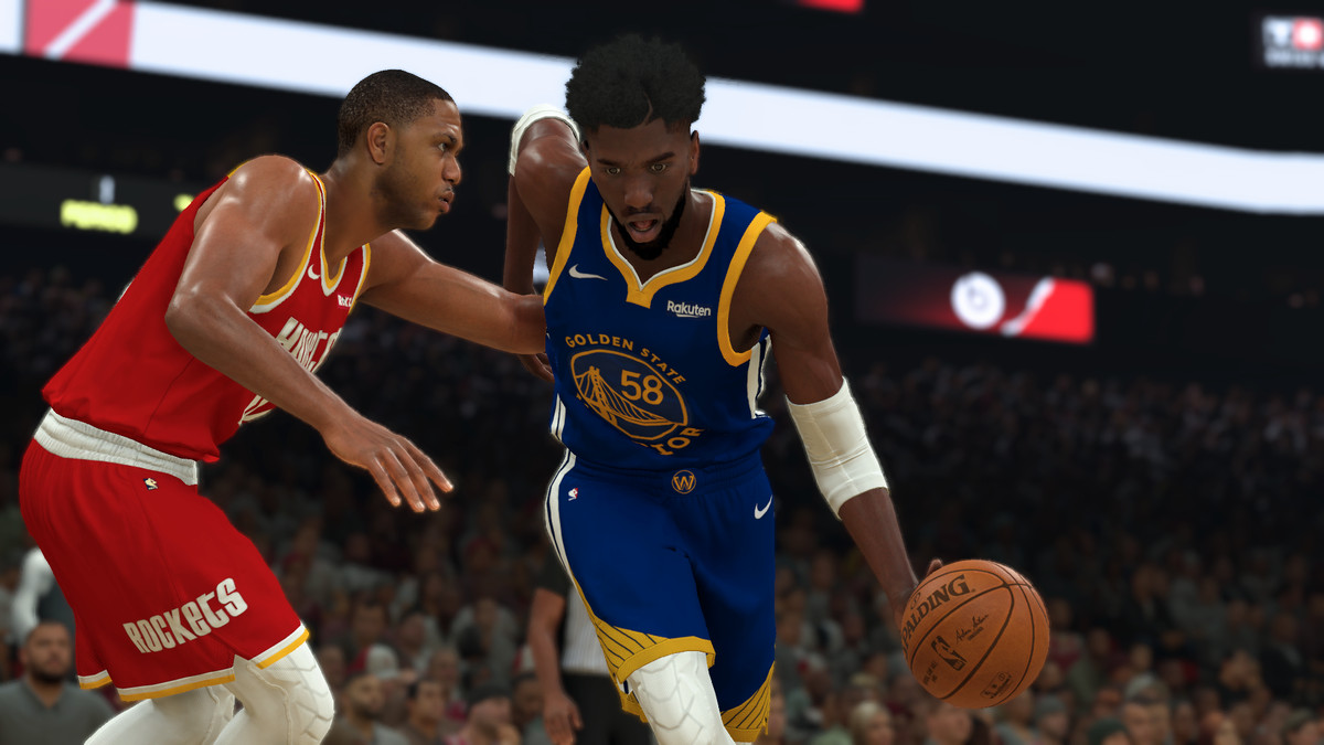 A player with the Golden State Warriors dribbles by a defender in a Houston Rockets throwback uniform