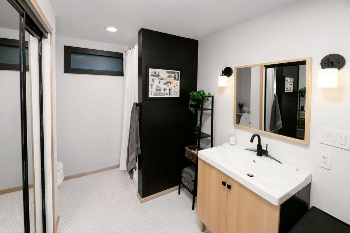 Ванная комната с белой раковиной и шкафом из натурального дерева под ней.