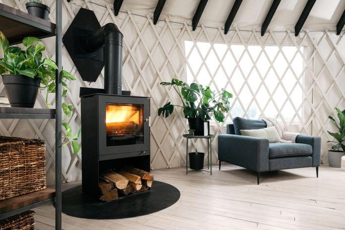 Черная печка топит белую решетчатую юрту, с растениями и серым креслом на картине.