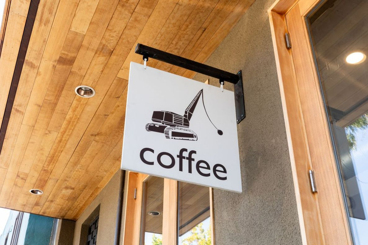 A white sign with a picture of black wrecking ball truck and the word coffee