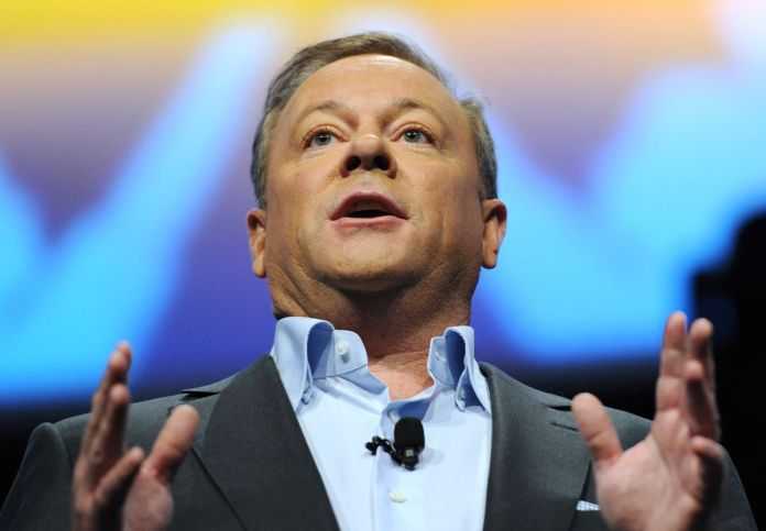 a close-up of Jack Tretton, a middle-aged man in a light blue dress shirt and dark gray jacket, speaking at Sony's E3 2013 PlayStation press conference