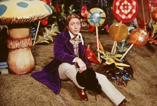 Gene Wilder as Willy Wonka, sitting amongst giant candies.