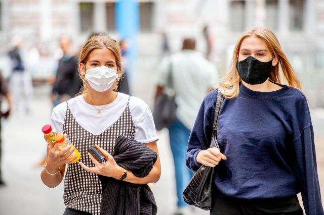 People wearing face masks as a preventive measure walk on...