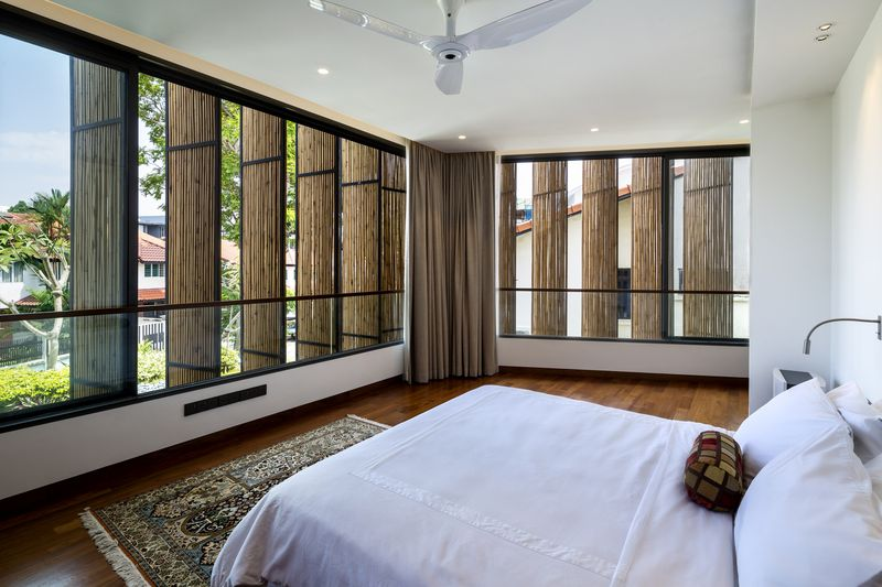 Bedroom with bamboo screens on windows.