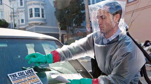 """In a scene from Contagion, Jude Law wears a homemade grey inflatable Hazmat suit with a square translucent bubble over his head as he distributes flyers reading """"The CDC lies, they collaborate with pharmaceutical companies, there is a cure."""""""