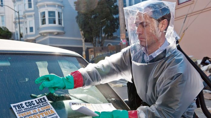 "In a scene from Contagion, Jude Law wears a homemade grey inflatable Hazmat suit with a square translucent bubble over his head as he distributes flyers reading ""The CDC lies, they collaborate with pharmaceutical companies, there is a cure."""