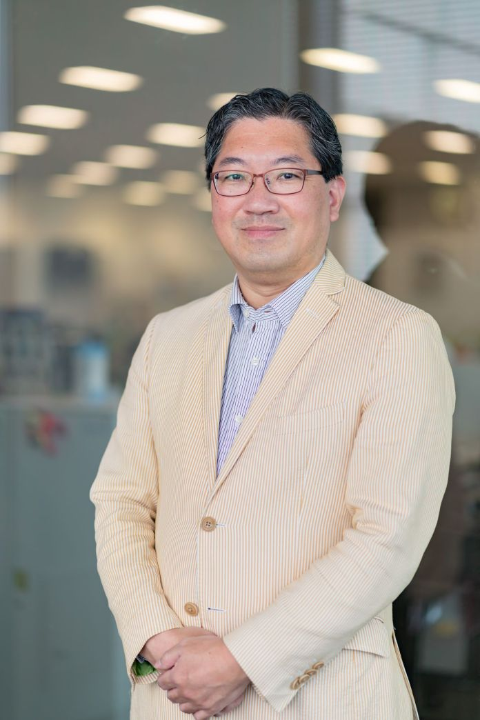 A photo of Yuji Naka standing in an office