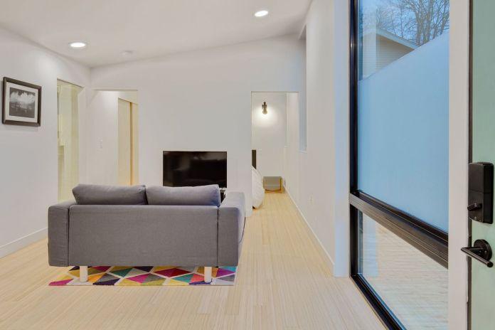 Интерьер дома с белыми внутренними стенами, светлыми деревянными полами и большими стеклянными окнами. Из гостиной открывается вид на вход в спальню.