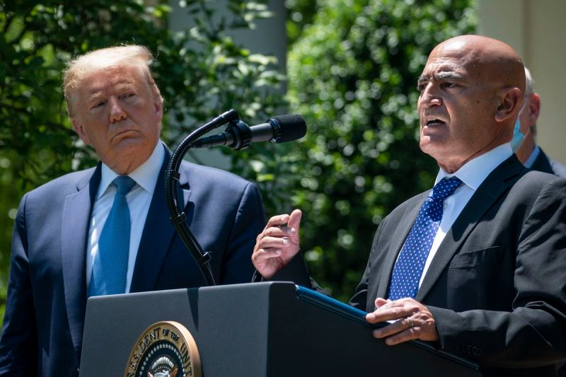 President Donald Trump listens as Moncef Slaoui, the former head of GlaxoSmithKlines vaccines division, speaks about coronavirus vaccine development in the Rose Garden of the White House on May 15, 2020 in Washington,