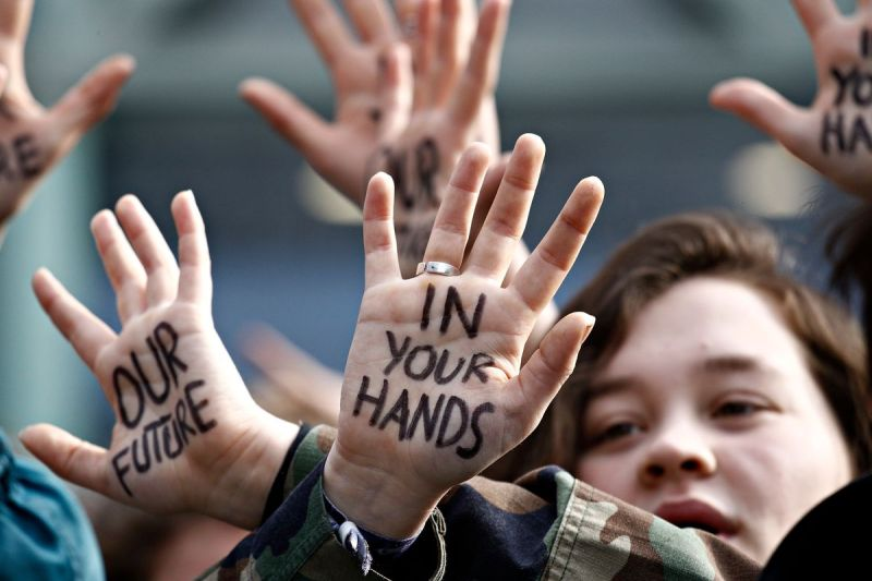 "Protestor with ""Our future in your hands"" written on their hands."
