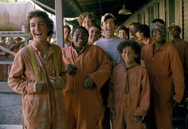 Stanley Yelnats (Shia LaBeouf) and friends laugh outside their bunk in a screenshot from Holes