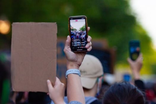 A protester holds up a phone that is live-streaming a video.