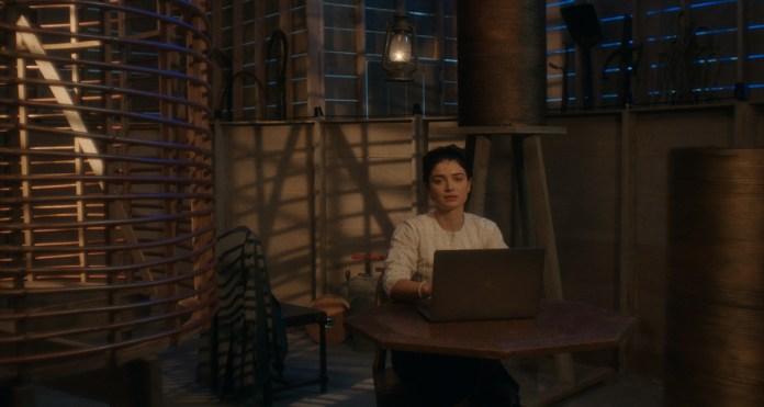 a woman sits behind a laptop