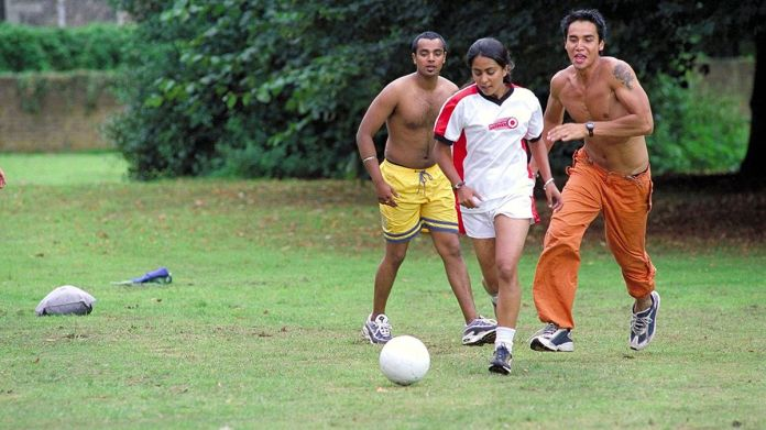 Jess (Parminder Nagra) plays football in the park with two shirtless men in a screenshot from Bend it Like Beckham