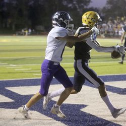 Bonneville's Reiss Graybeal completes a pass in the end zone to score a touchdown as Box Elder's Jace Robinson guards him during a football game at Bonneville High School in Washington Terrace on Friday, Oct. 9, 2020. Bonneville won 42-14.
