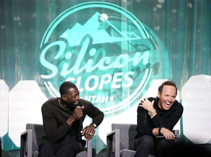 Dwyane Wade, part owner of the Utah Jazz, left, and Jazz owner Ryan Smith laugh as they talk about rebranding effort for the team at the Silicon Slopes Summit at the Salt Palace in Salt Lake City on Wednesday, Oct. 13, 2021.