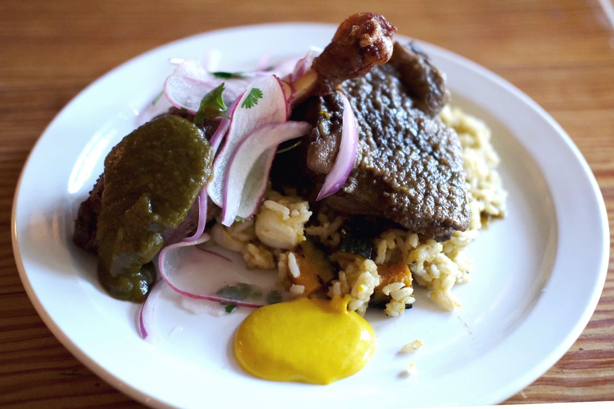 Arroz con pato, a main course of braised duck thigh, confit fried leg, salsa criolla and huancaina sauce from Atlanta Peruvian pop-up La Chingana