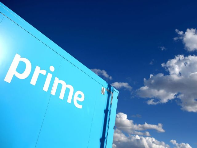 """A corner of a truck with the word """"prime"""" on it against a blue sky with white clouds."""