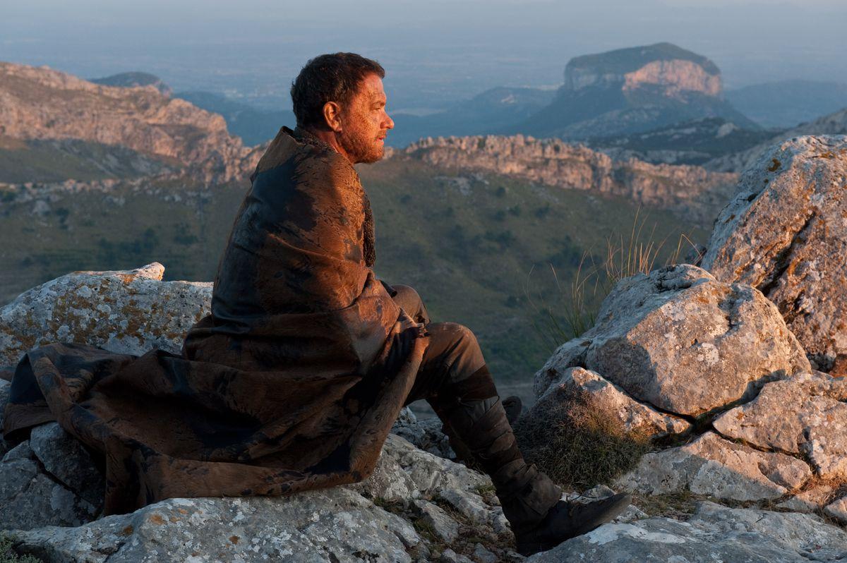 Cloud Atlas - Zachry envuelto en una manta sentado sobre rocas