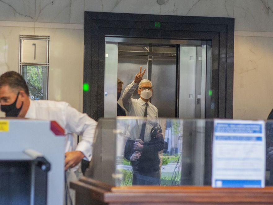 Apple CEO Tim Cook gives cameras a peace sign as he steps into an elevator.