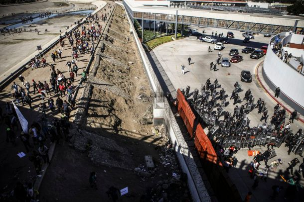Mexican police stand guard (R) as migrants walk on a bank of the nearly dry Tijuana River as they make their way toward the El Chaparral port of entry, after circumventing a police blockade, on November 25, 2018 in Tijuana, Mexico.