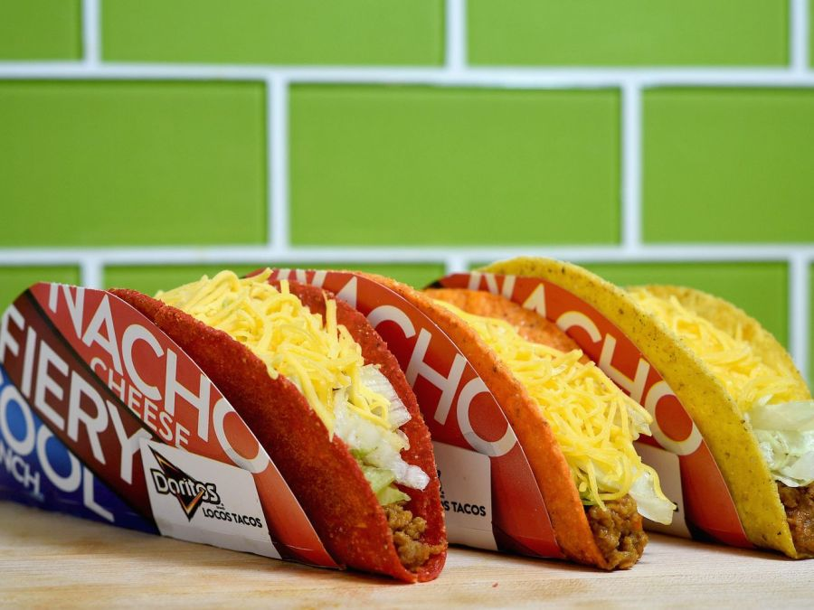 Three Taco Bell Doritos Locos Tacos in front of a green tile wall