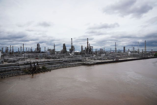 A distant landscape photo of an oil refinery along a river on a cloudy day.