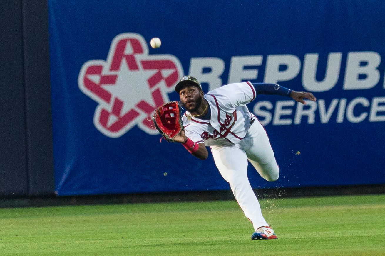 Michael Harris is about to make a running catch in a night game for the Rome Braves. His eyes are locked on the ball in the air just a foot in front of him, and he is bent over at the waist attempting to make the play.
