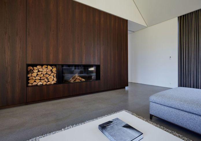 В открытой гостиной серая секция выходит на деревянную стену в полный рост из краснодеревщика, оснащенную современным камином и дровами.