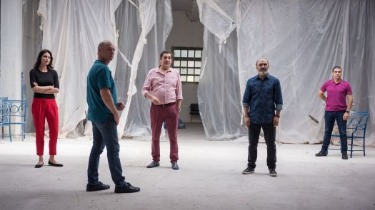A group of colorfully dressed people stand in a warehouse.