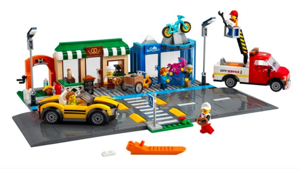The new official shopping street Lego set has a large street and a small blue bike lane next to small shops.