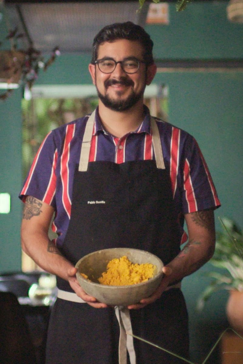 A chef in an apron holds a bowl with something yellow inside.