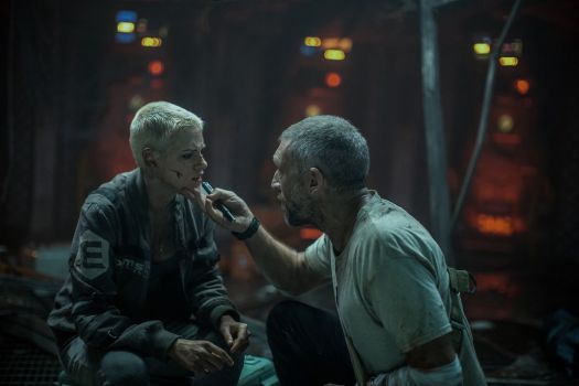 In a control room, the Captain (Cassel) inspects Norah's (Stewart) facial wounds in Underwater