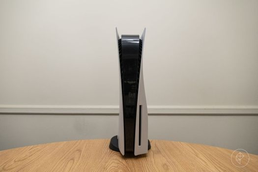 a wide photo of the PlayStation 5 standing vertically on a round wooden table