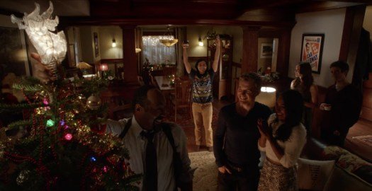 The West family celebrates Christmas with friends, cheering as Joe West (Jesse L. Martin) tops the family tree with an angel in The Flash.
