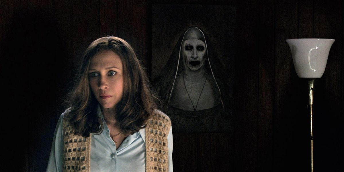 Vera Farmiga as Lorraine Warren stands in front of a creepy nun portrait in The Conjuring 2