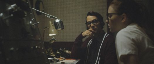 A young man and woman, both in heavy 1950s glasses, sit at a counter in front of an old-school heavy radio mic in The Vast of Night.