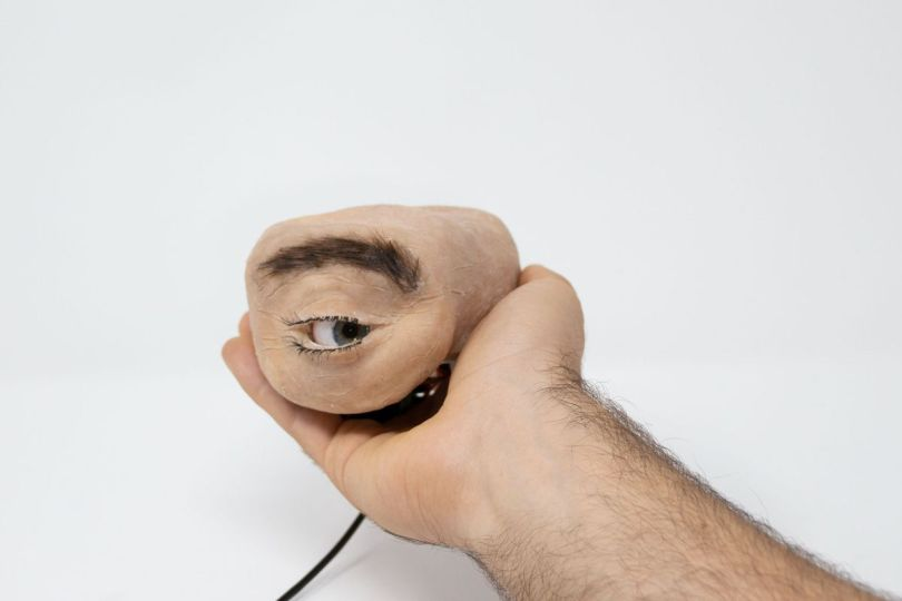 A person's hand tenderly holding a chunk of synthetic flesh with an eyeball in it glancing to the right. There's a cord coming from the back of it.