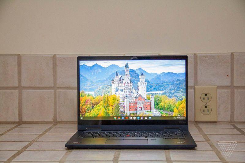 Il Chromebook Lenovo ThinkPad C13 Yoga visto di fronte su un bancone piastrellato.  Lo schermo mostra un castello bianco circondato da alberi con montagne sullo sfondo.